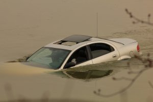 A car submerged in the river and stuck on the sandbar